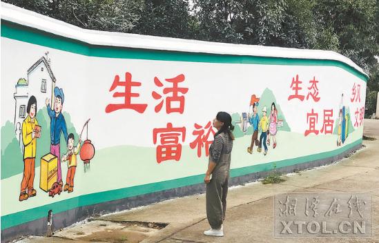荷塘村内关于精神文明建设的手绘壁画。(记者 陈旭东 摄)