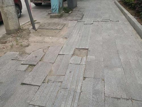 卫健局东侧人行道路面破损,垃圾堆待清